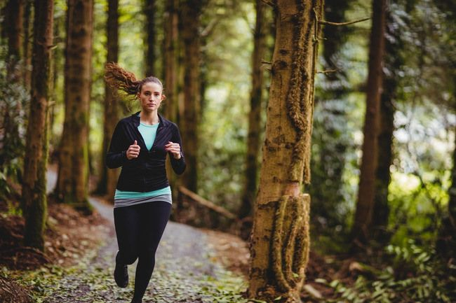 Fit brunette jogging in the woods