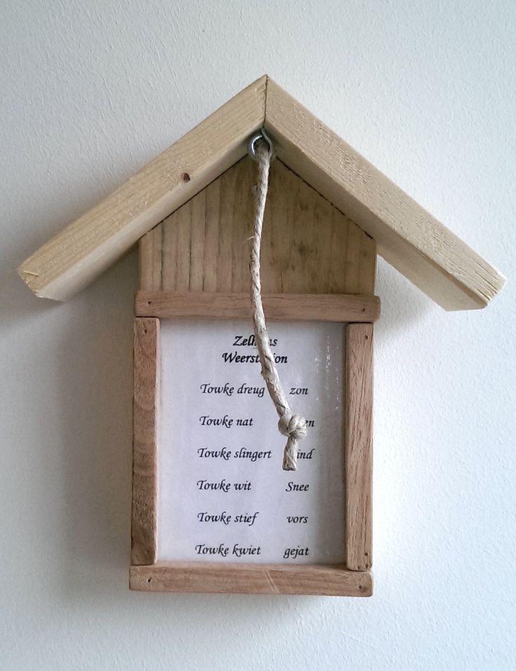 Een 'weerstation' gemaakt van hout en een touwtje dat aangeeft wat het weer doet.