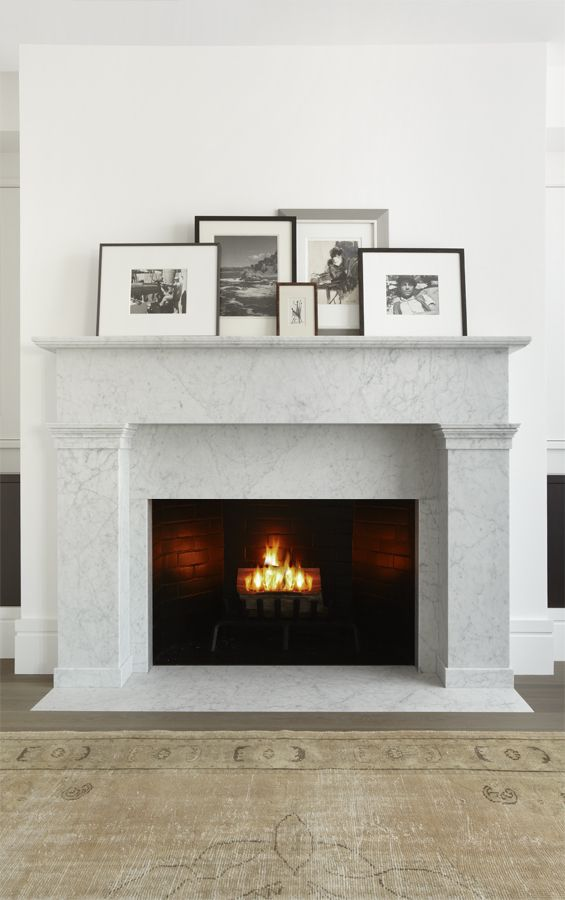 luxurious marble fireplace with layered photographs find more inspiration via