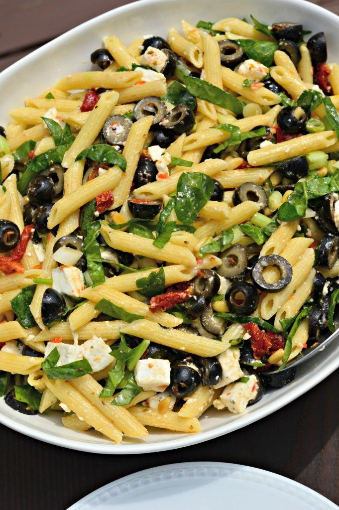 Penne pasta salad with black olives, sun-dried tomatoes, feta and spinach: a light vegetarian dinner or healthy summer side