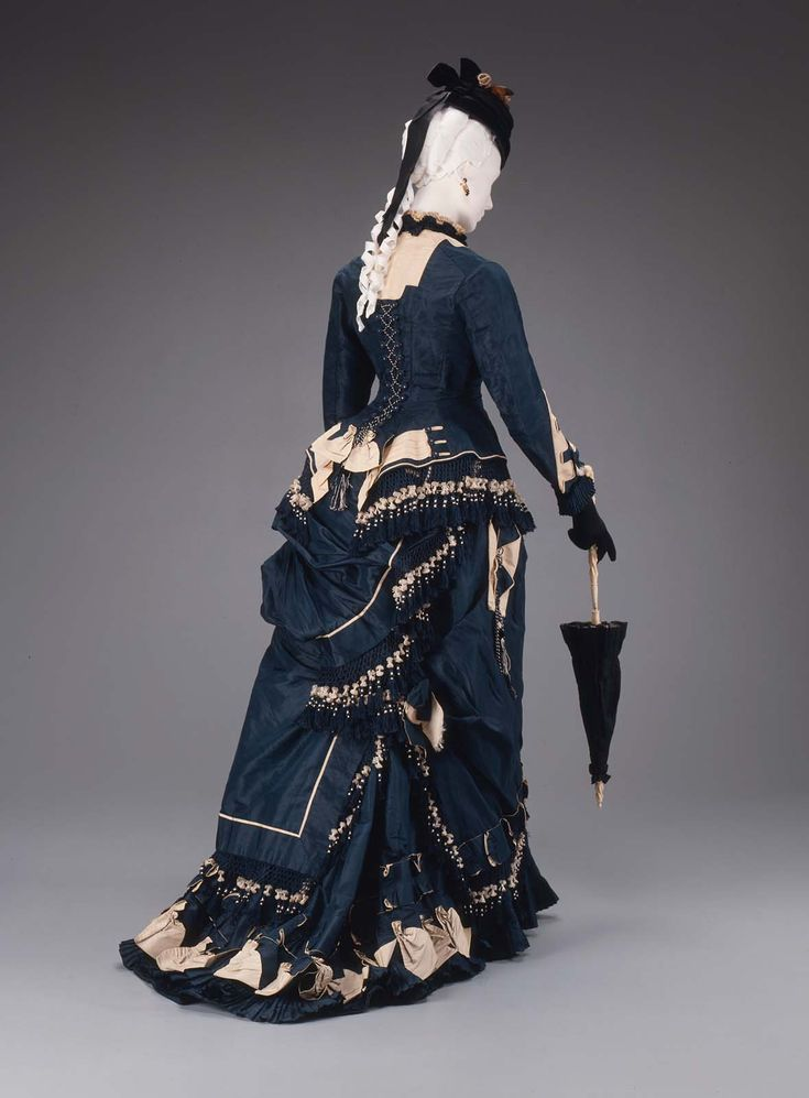 "Two-piece dress of Prussian blue and ivory corded silk. Fitted jacket bodice, blue, trimmed at bottom with blue and white knotted net and tassels; high round neck trimmed with ruching; at neck and on sleeve fronts, insertions of ivory silk edged with flat blue tabs. Blue skirt, elaborately trimmed with buttons, piping, net and tassels, ruchings, pleatings and tabs; bustle and short train. Label on tape inside bodice: ""John J. Stevens, Importer and dealer in Paris modes / 282 Washing..."