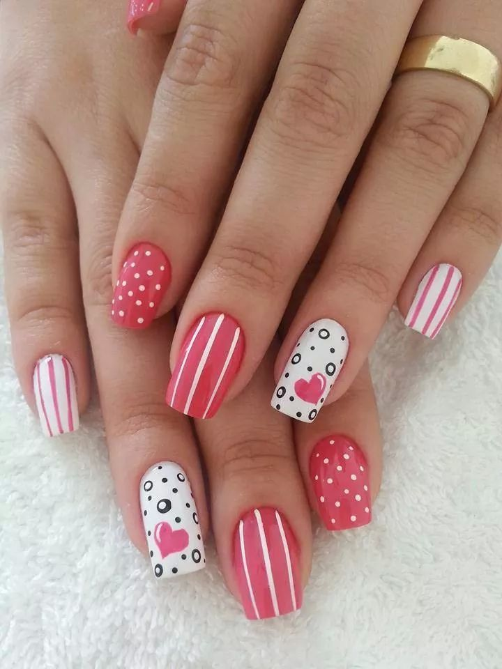 Uñas decoradas en color rosa con corazones