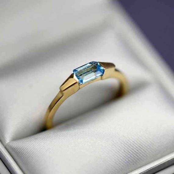 Les photos sont prises avec un objectif Macro, ce qui fait paraître le bijou plus grand que la réalité, lisez attentivement les dimensions, merci. ********************* 1>> Bague en or jaune massif 18k sertie dune topaze bleue 2>> Topaze bleue : 0,65ct en forme de baguette (La pierre est