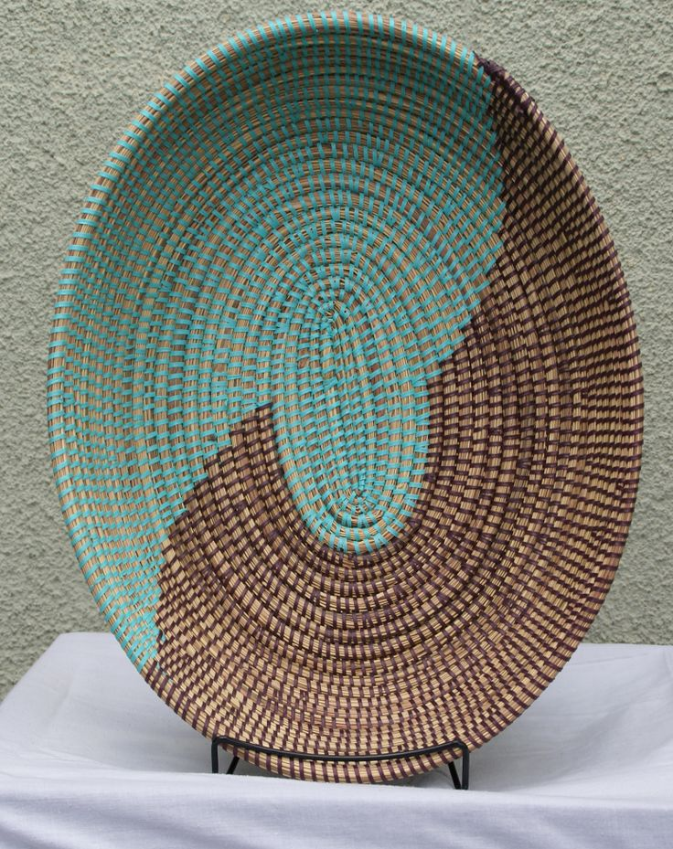 "Wolof Medium Oval Basket Bowl 50 brown/50 turquoise. Great for fruit basket, coffee table, dining table or as decorative wall hanging or shelf display.  Dimension: 15"" Height  X 12 ""Width  X 3"" Depth  Weight: approximately 10 ounces  Material: Recycled plastic prayer mat, local grass, called njodax or typha"