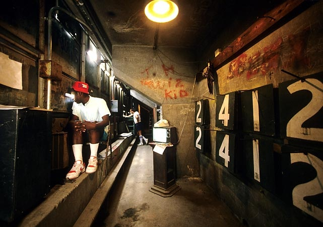 The inside of the Green Monster is a part of Fenway Park many fans never get to visit. In this 1987 photo, a worker watches a game against the Yankees.  Photographed by: Walter Iooss Jr./SI