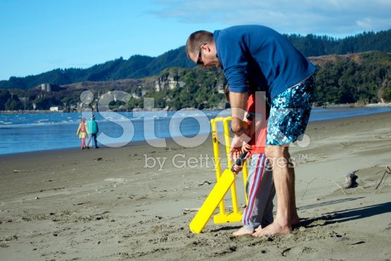 Man and Boy Playing Cricket on Beach royalty-free stock photo