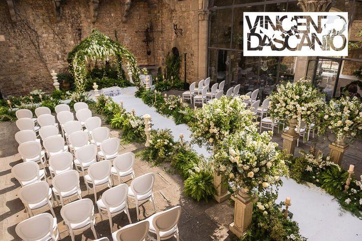Bucolic organic aisle, greenery and white flowers compositions in medici vases at castello di vincigliata,
