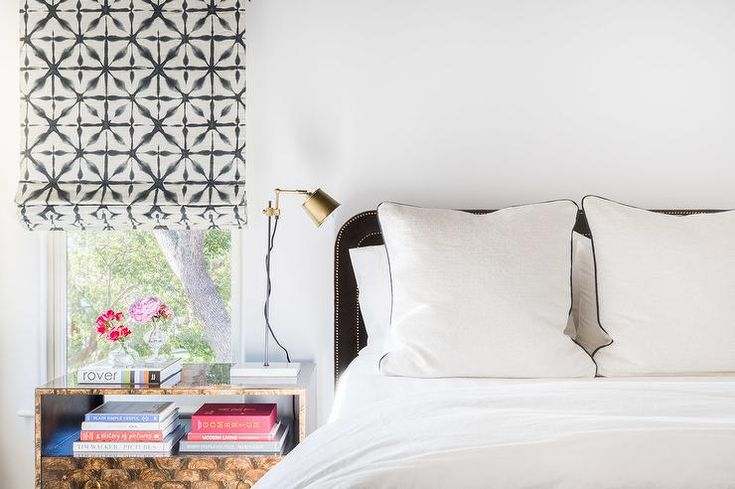 Alyssa Rosenheck - Oxford Design Studio -  Chic contemporary bedroom boasts a window covered in a black and white roman shade hung over a burl wood nightstand topped with a brass swing arm roman shade.