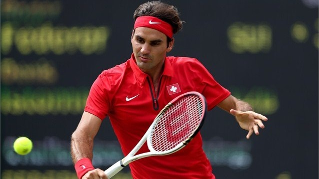 Roger Federer of Switzerland returns a shot to Denis Istomin of Uzbekistan during the third round of men's Singles Tennis on Day 5 of the London 2012 Olympic Games at Wimbledon.