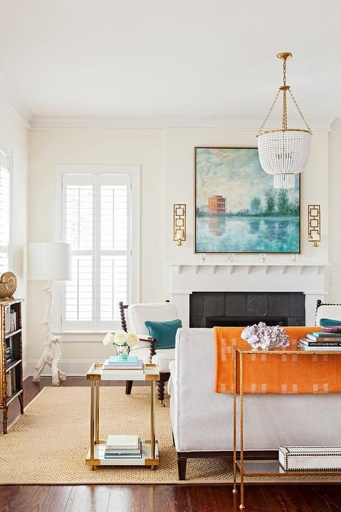 White and blue living room features an Aerin Jacqueline Chandelier illuminating a white sofa draped in an orange blanket placed next to a white and gold end table, Bernhardt Brielle End Table.