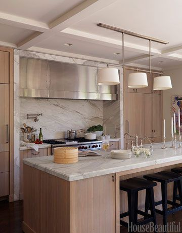 In this modern Los Angeles kitchen, architect William Hefner balanced the oak wood with a Calacatta gold marble backsplash and a matching island.