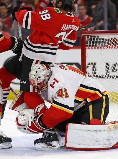 CHICAGO, IL - FEBRUARY 06: Mike Smith #41 of the Calgary Flames grabs the leg of Ryan Hartman #38 of the Chicago Blackhawks after they collide at the United Center on February 6 2018 in Chicago, Illinois. (Photo by Jonathan Daniel/Getty Images)
