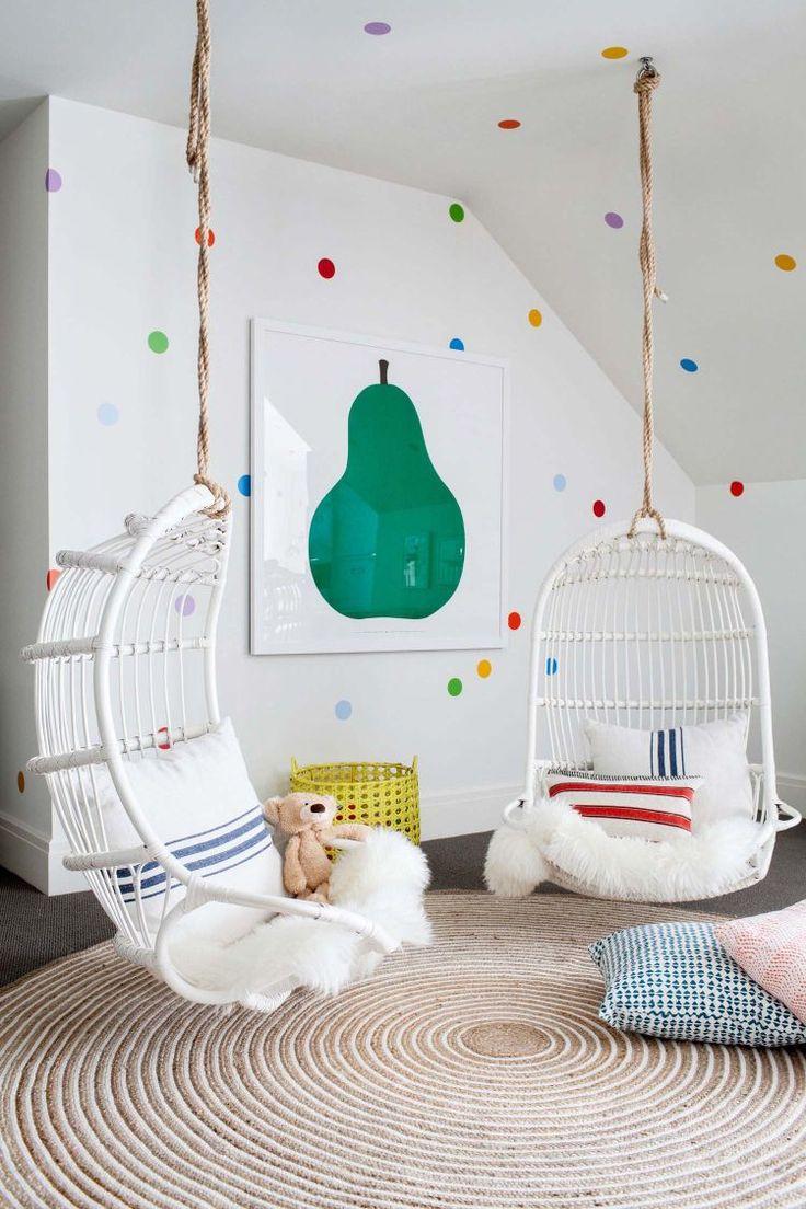 Spielzimmer mit gemusterten Wänden und bequemen Hängesesseln