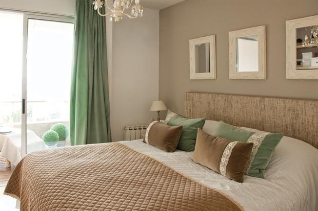 Sobre el cabecero tapizado en rafia, tres espejos heredados. Pie de cama en pana con borde en crochet y almohadones color visón y aguamarina
