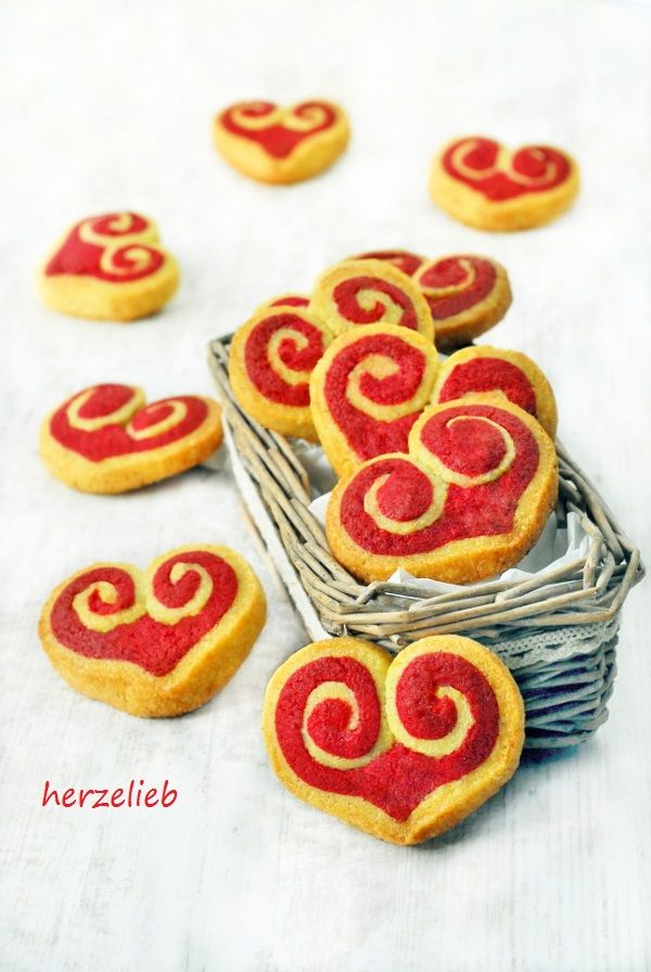 Two tone heart sugar cookies flavored with orange zest, vanilla, and cinnamon (in German). Roll out dough halves so they are about 1.5cm (.6 in) tall when stacked and about 25 cm (9.8 in) wide at short end. refrigerate a 2nd time, then cut 1cm (.4 in) slices, roll up from each side like a snail, then pinch the bottom to make a point and fill any holes with red dough, then bake. Einfaches und leichtes Rezept für Herzkekse.