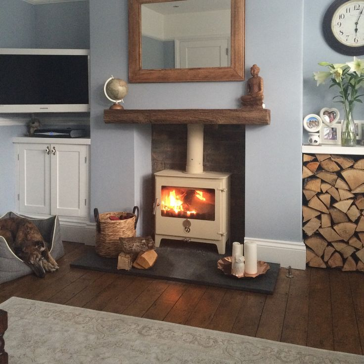 cozy living room chilli penguin log burner slate harth varnished floorboards blue grey walls
