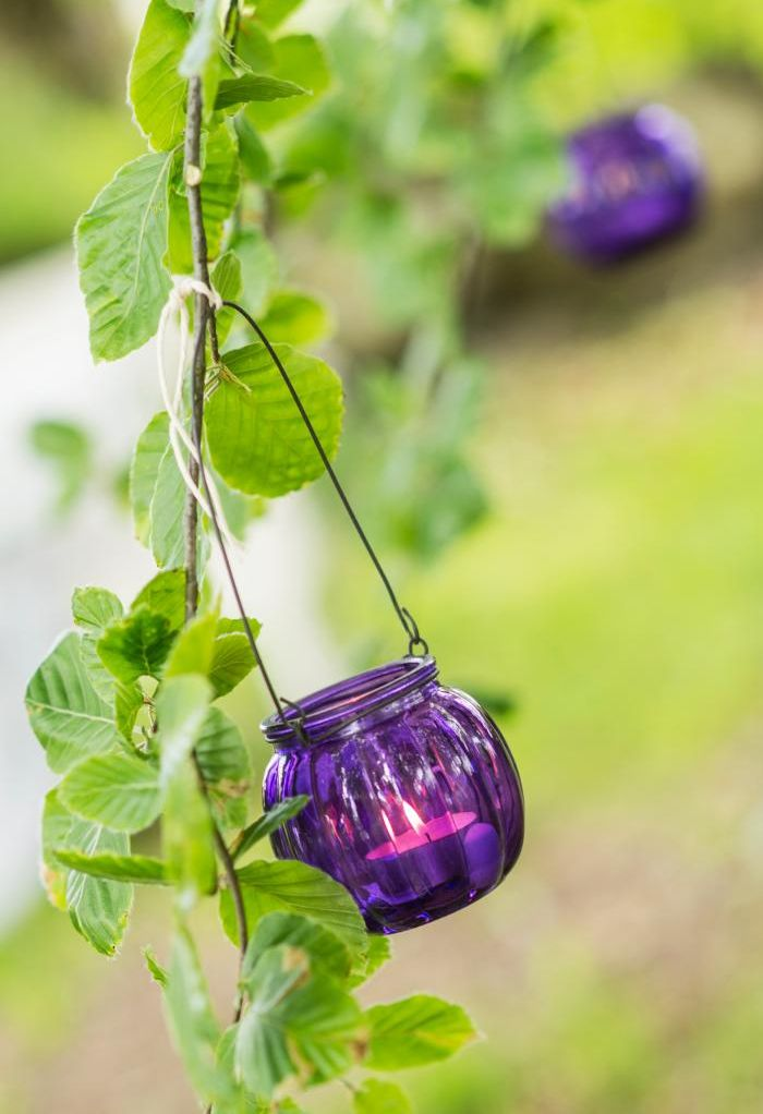Purple glass votive holders hanging off branches....love it