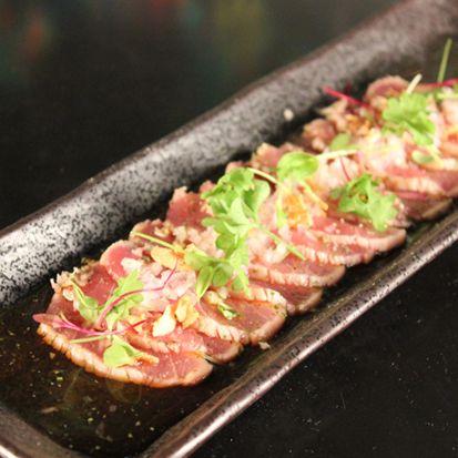 Yellow Fin Tuna Tataki with Fried Garlic, French Onion, Light Citrus Sauce & Fresh Herbs - Chef's Pencil