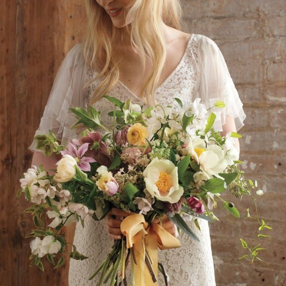 This bouquet bursts with a mix of peonies, tulips, clematis, lilacs, and apple branches.