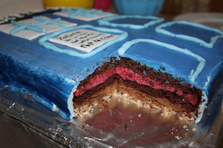 Tardis kage med kig til fyldet:  Nødde bund, chokoorangecreme, chokobund, bærmousse,chokobund pynt: kombination af glasur og sugarpaste og masser af Tardis blå