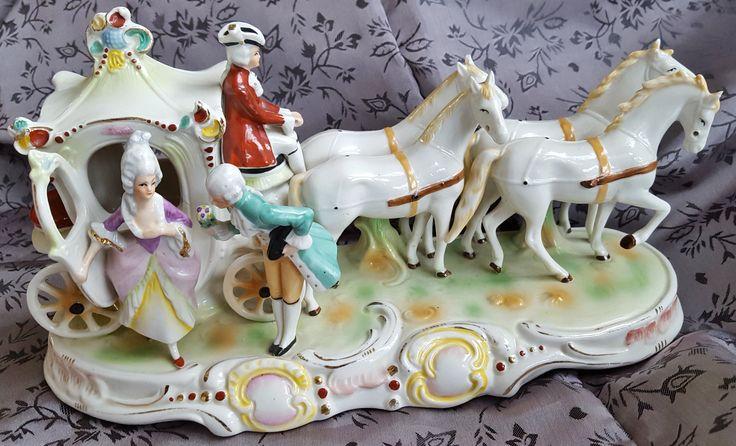 Midden 20e eeuw, Duitsland Porseleinen paardenkoets, Graefenthal. Gemerkt met 1859 en kroontje. Gedetailleerd met authentieke beschildering en zonder kleurvervaging. Op de achterkant staan de nummers 20312 en tekst Germany Het porseleinen beeld van een dame en een heer bij prachtige koets met 4 paarden en koetsier op de bok. Er zijn helaas twee kleine chipies af bij de oren van het paard dit is zeker niet storend. Verdere staat van zowel het porselein als de kleuring zijn in goede staat.