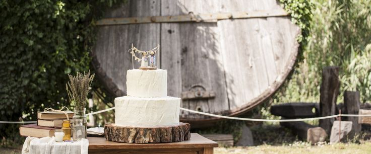 Torta spatolata di panna, su base di legno. Decorazione floreale con lavanda, tavolo in stile country.