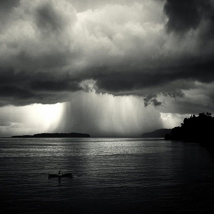 Beautiful black and white landscape photography showing rain clouds over the sea waterfall bandaneira east indonesia photographed by hengki