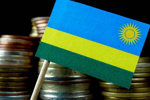 rwanda flag waving with stack of money coins macro