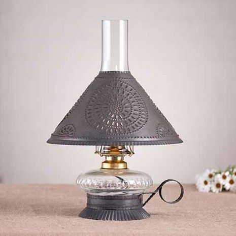 """This Cupid Electrified Oil Lamp comes with a decorative, punched tin chisel design shade and is available in either a blackened tin or rustic tin finish. It measures 15"""" high x 10"""" wide with shade. One standard socket (60 watt bulb maximum), 7 feet cord, glass chimney included. Handcrafted in Pennsylvania. UL approved and comes with a 5 year warranty."""