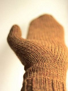 A pair of mittens with cables and biased thumb gusset knitted with worsted weight yarn.