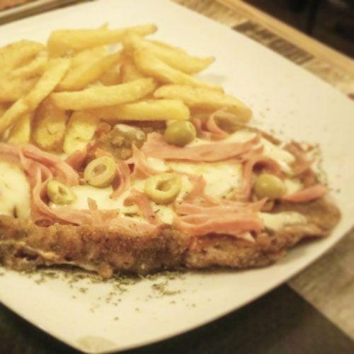 Milasa de ternera a la napolitana, con jamón, salsa de tomate, queso fundido y olivas preparado en el restaurante argentino La Neura de Barcelona
