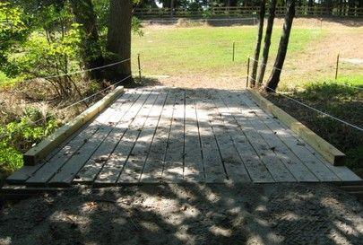 "Here the horses cross the creek on the ""track"" using a bridge. The bridge was built from2x12x16- 2' on center. The decking is 2x6's run perpendicular to the stringers, then another layer of 2x6s run parallel. This is to insure that the horses cannot punch through the decking. The approaches are dirt with gravel top dressing. This design came from the USFS manual on trail bridges. The bridge will easily hold the golf cart (muck machine) and the small Kubota."