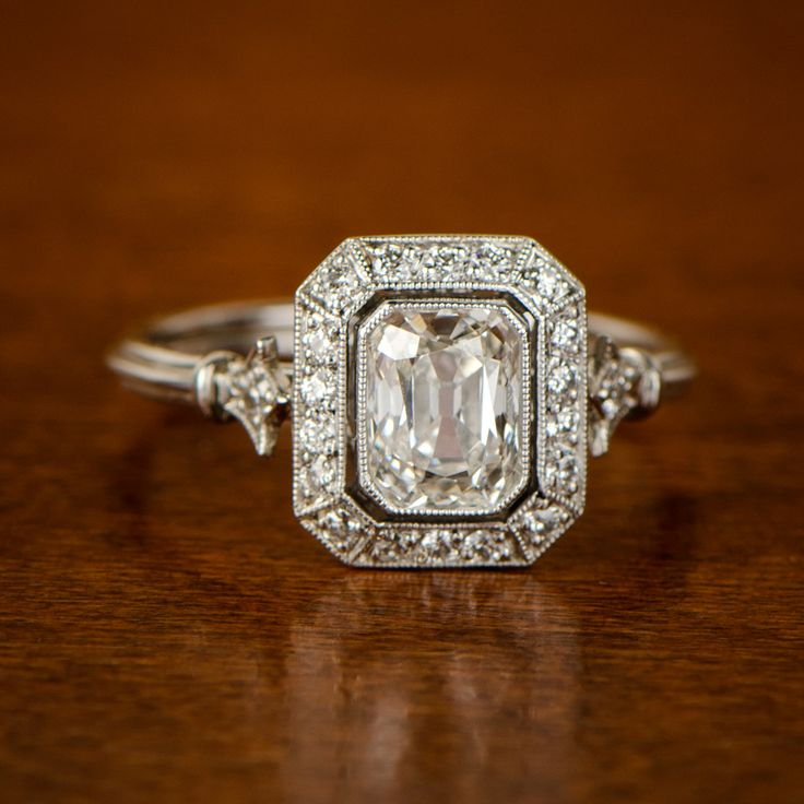 A beautiful halo diamond engagement ring, featuring a beautiful antique mixed emerald cut.