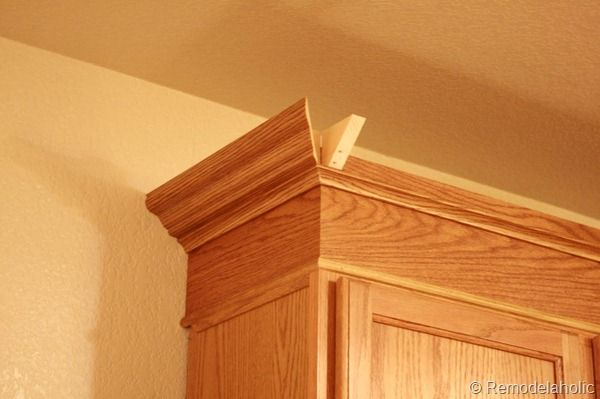 UPGRADE: Oak Kitchen Cabinets With crown mouldings to replace the UGLY railing trim that in on it now.....I will not be painting my cabinets since he loves the wood look.