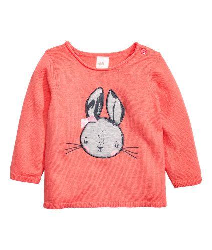 Koraal/konijn. Een fijngebreide trui van een zachte katoenmix met een applicatie voor. De trui heeft een oprollend randje rond de halsopening en een knoop