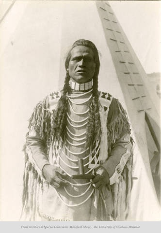 Joe Malta, Kootenai and PendOreille Indian, holding pipe;  posing in front of tipi. Location unknown.  Date: unknown