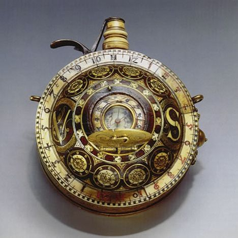 16th century German pocketwatch that includes a gunpowder flask, compass and sundial. The rosewood flask is decorated with ornaments of brass and bone, and at the top is the bone funnel used to insert the gunpowder. Beneath the small lid in the center of the piece is a sundial; a string gnomon is exposed by opening the lid and can tell the hours from 6 am to 6 pm.