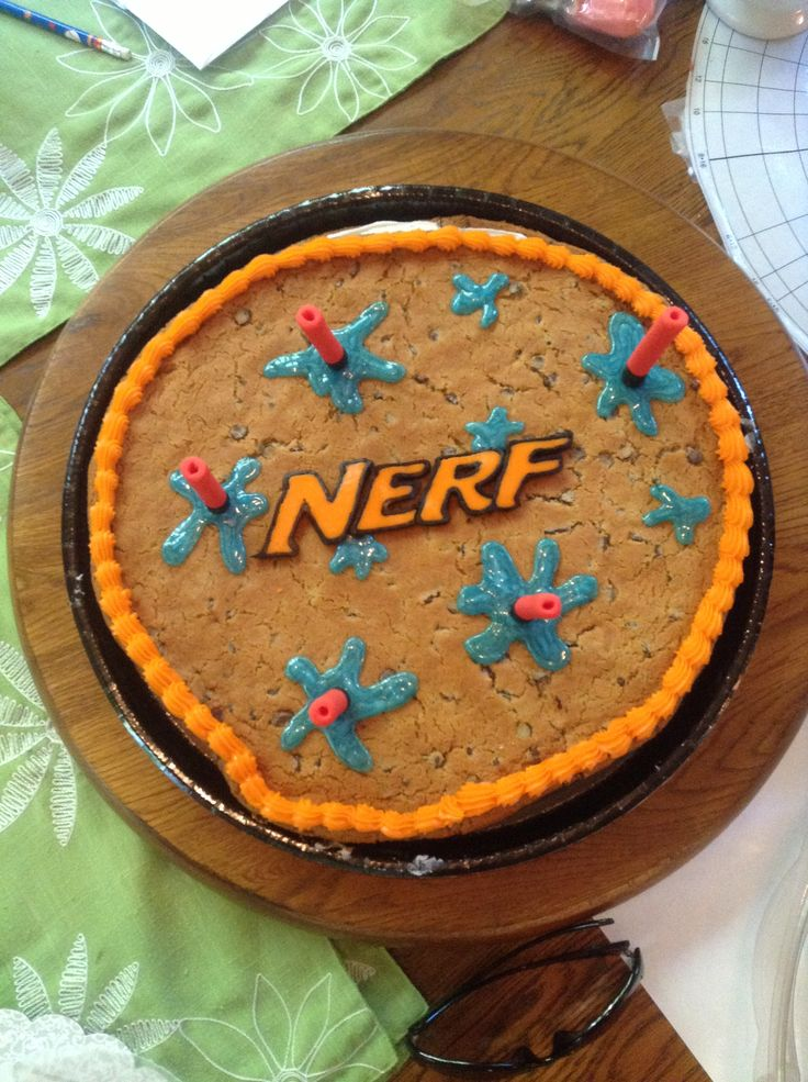 Nerf cake I made for a friend's Nerf water gun party. Bought undecorated cookie cake from Sam's. Made darts from fondant. Used frozen icing technique from Pinterest for words and free handed water spots with Wilton sparkle gel.