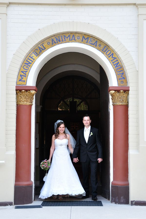bride and groom stepping through the church's door hand in hand