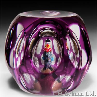 "Perthshire Paperweights 1998 ""Jojo the Clown"" faceted amethyst-flash overlay paperweight. A three-dimensional lampwork clown, poised atop a small podium, peers out through one of eight upper oval facets above a row of eight round lower facets within an amethyst-flash overlay."