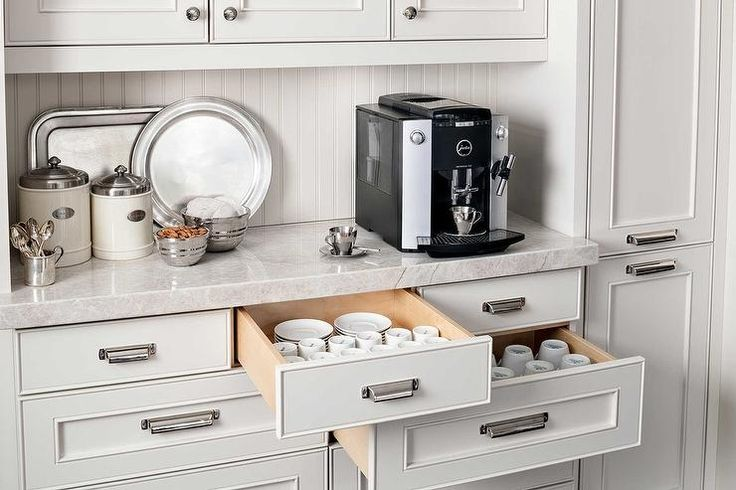 Kitchen coffee station nook features raised panel cabinets paired with gray quartzite countertops and a beadboard backsplash. An espresso machine sits atop drawers filled with coffee cups and saucers.