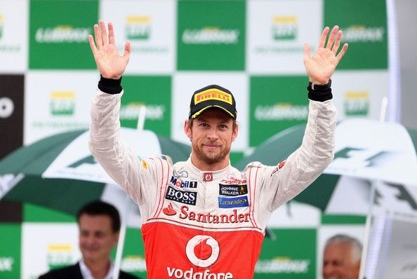 Jenson Button of Great Britain and McLaren celebrates on the podium after winning the Brazilian Formula One Grand Prix