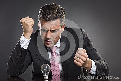 Portrait of angry businessman with clenched fists looking at light bulb, seaking desperately for smart business solution over dark background.