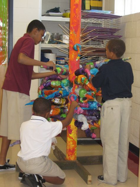 Chihuly Art Lesson: water bottle, covered in foil and extended out, then covered in tissue paper/glue (for shiny effect.) Then, attached to tall sculpture using 2x4 and dowel rods