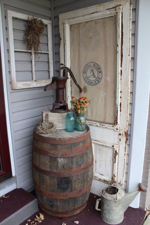 Primitive outdoor decorating. Whiskey Barrel, Old door, feed sack, window frame, pump, watering can. Bird nests.