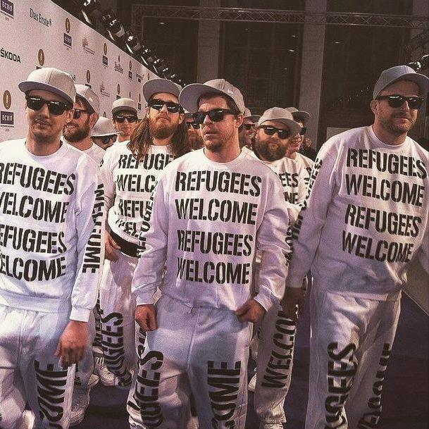 """http://polyprisma.de/wp-content/uploads/2015/08/Deichkind-Refugees-Welcome-Pro-Asyl.jpg Deichkind sagt: Refugees Welcome - Du auch? http://polyprisma.de/2015/deichkind-sagt-refugees-welcome-du-auch/ Deichkind liefert – mal wieder. Das Thema Flüchtlinge und Asyl ist in aller Munde und viele versuchen auf ihre Art zu helfen – irgendwie wenigstens. Auch die Jungs von Deichkind dachten sich """"Hey, Spenden ist geil"""" und kreierten das typisch Deichkind ex"""