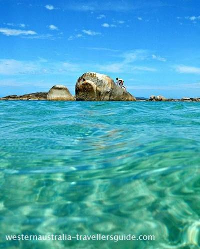 Climbing a rock at Greens Pool, a beautiful beach near Denmark on Western Australia's south coast. • rock pool Australia