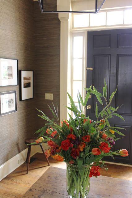 Dark gray door, windows around the door, molding and sea grass wallpaper