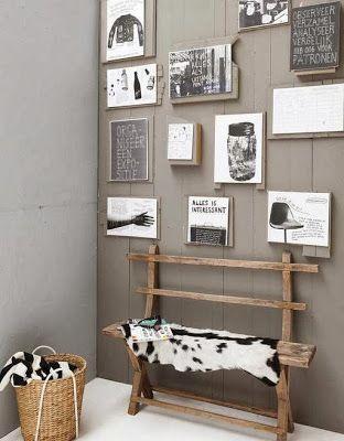 Een warm-grijze wand met alleen maar decoratie in zwart-wit.