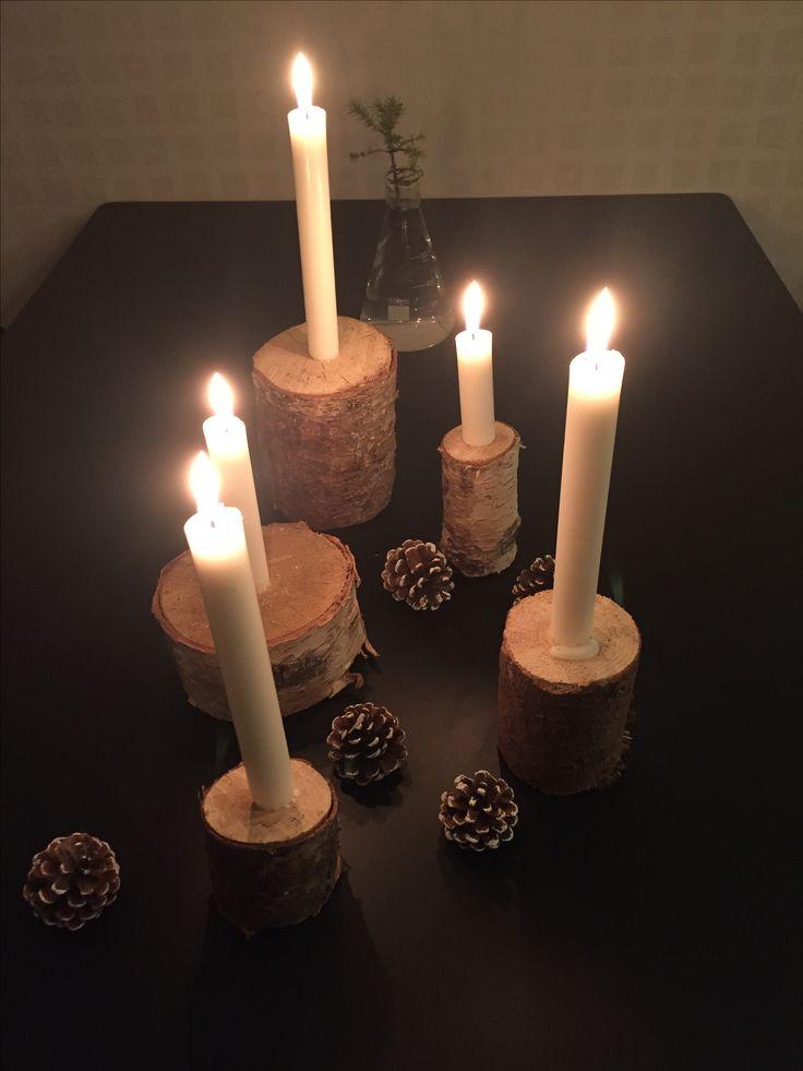 Egentillverkade ljusstakar och vitmålade kottar.